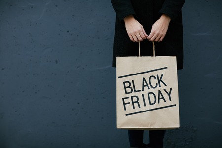 paperbag: Young woman in black holding paperbag with note Black Friday