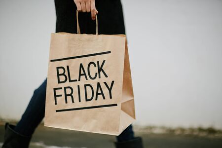 paperbag: Young woman in black carrying paperbag on Black Friday Stock Photo
