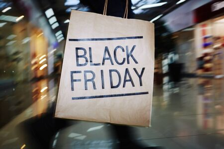 paperbag: Shopaholic with Black Friday paperbag moving in the mall