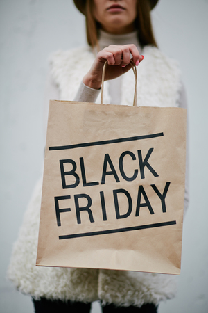 paperbag: Young woman showing Black Friday paperbag