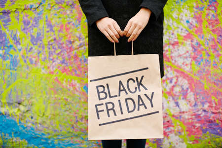paperbag: Girl in black holding paperbag announcing Black Friday