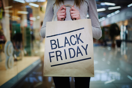 shopper: Young shopper showing Black Friday paperbag in the mall