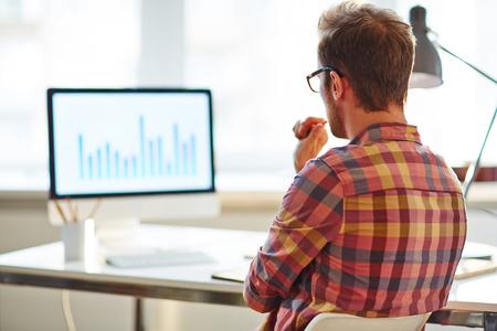 biznes: Biznesmen siedział przy stole i myśli o projekcie