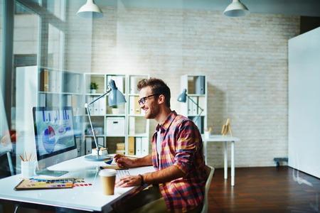 Vrolijke jonge kantoormedewerker werken op de computer op zijn kantoor