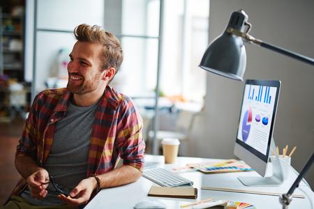Neformální mladý podnikatel sedí na svém pracovišti