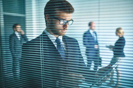 businessman suit: Businessman reading a document behind jalousie with his colleagues