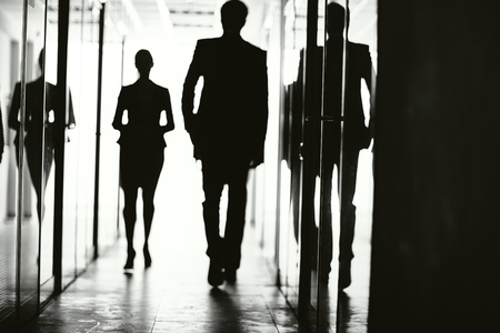 people walking: Silhouettes of business people walking at office Stock Photo