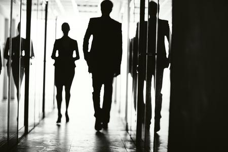 personas caminando: Siluetas de la gente de negocios a pie en la oficina