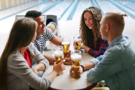 bolos: Grupo de amigos bebiendo cerveza en club de bolos