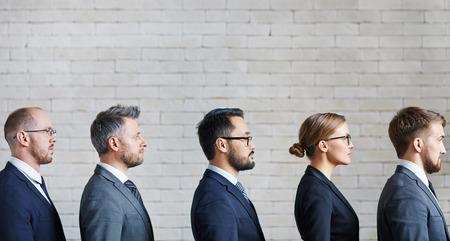 Grave equipo de negocios de pie en una fila