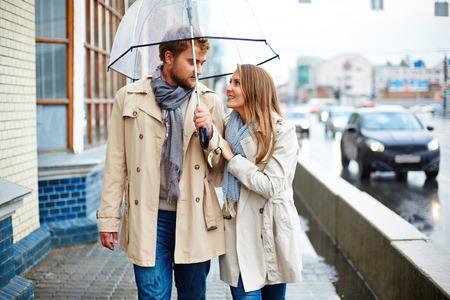 sotto la pioggia: Coppie belle sotto la pioggia per la strada