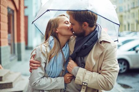 雨の中で傘の下で恋愛する若いカップル