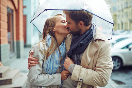 Loving young couple in love under umbrella in the rain. Stock Photo