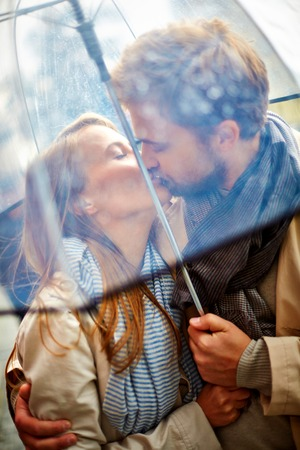 couple in rain: Beautiful couple kissing outside in the rain Stock Photo