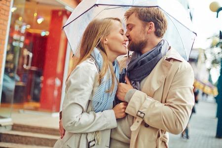 Romantisch paar kussen elkaar tijdens de regen Stockfoto
