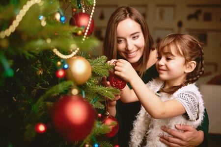 familj: Söt flicka och hennes mamma utsmyckning gran på julafton