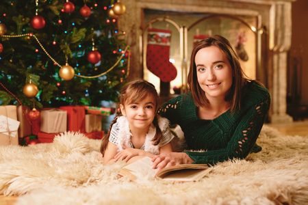 beautiful mother: Cute girl and her mother with book looking at camera on Christmas evening