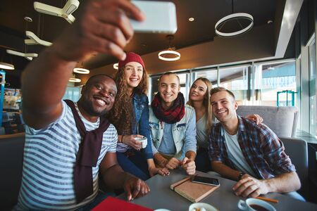 restful: Restful teenagers making selfie while sitting in cafe