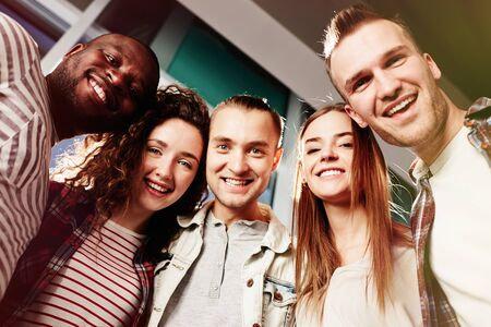 boy lady: Group of cheerful friends looking at camera with toothy smiles Stock Photo