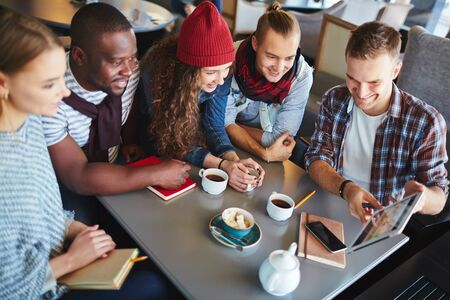 group of happy people: Group of friendly teens with touchpad networking in cafe Stock Photo