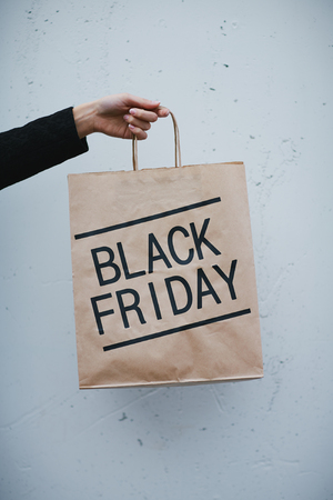 Female hand holding paperbag with note Black Friday