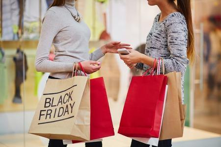 chicas de compras: Muchachas de compras con bolsas de papel que hablan en el centro comercial