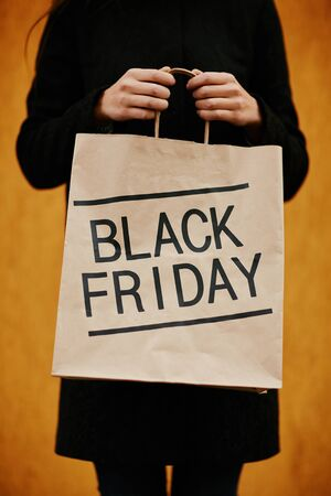 paperbag: Girl showing paperbag inviting to Black Friday Stock Photo