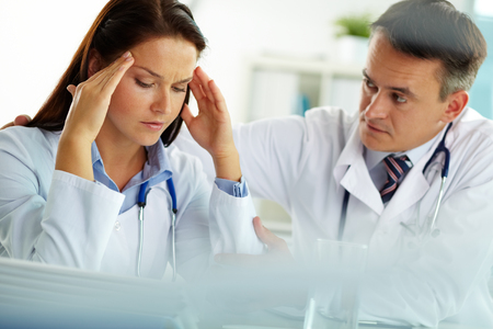 comforting: Doctor comforting his upset colleague Stock Photo