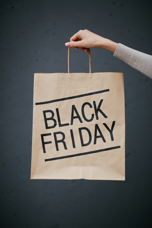 paperbag: Female hand with paperbag announcing Black Friday Stock Photo