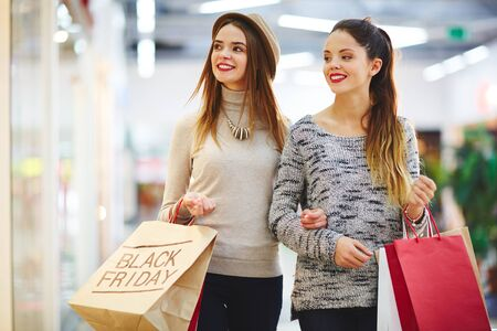 young people group: Two friendly girls on Black Friday sale