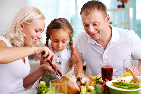thanksgiving adult: Family of three sitting at the table and going to eat roasted turkey Stock Photo