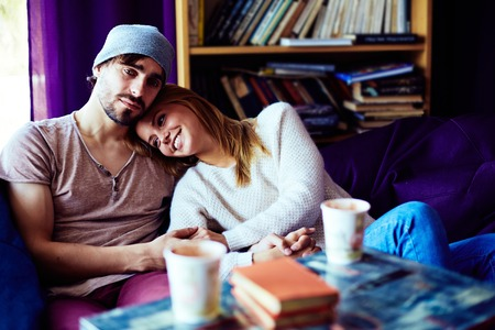 couples hug: Affectionate couple resting on sofa and enjoying each other
