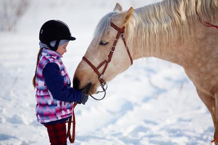 caballo jinete: Niña con el exterior del caballo en invierno Foto de archivo