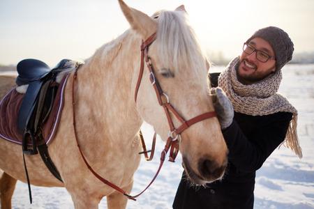 Lächelnder Mann sein Pferd umarmt Standard-Bild - 47784747
