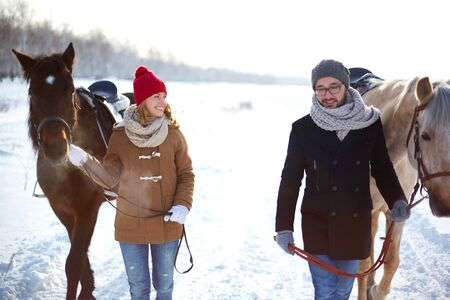 couple winter: Young happy couple with horses walking in winter day