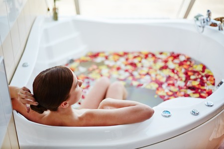Woman relaxing in bathtub with rose petals Stock Photo