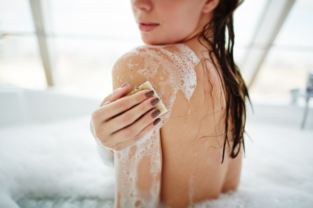 Young woman washing her body with soap at home