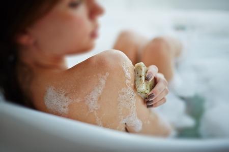 Woman washing herself in a bathtub