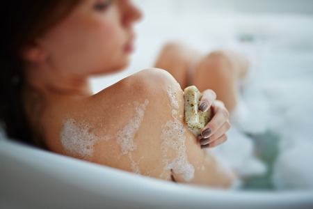 woman in bath: Woman washing herself in a bathtub