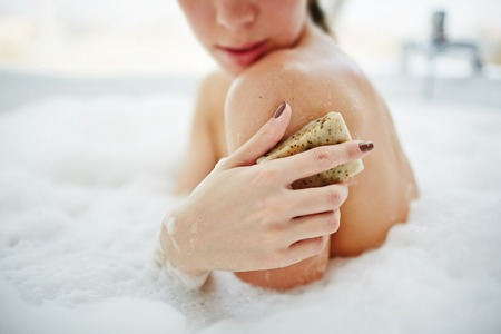 bath: Young woman scrubbing her skin in a bath Stock Photo