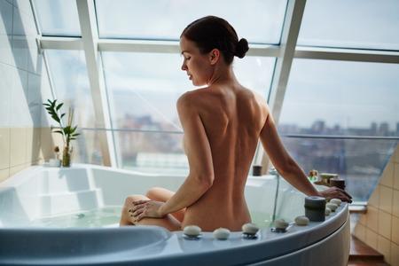 mujer desnuda de espalda: Mujer desnuda sentada en la ba�era en su cuarto de ba�o moderno