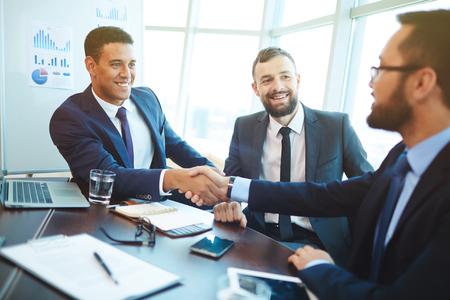Gelukkig zakenlieden handshaking na onderhandelingen in het kantoor