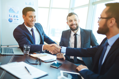 empresario: Hombres de negocios feliz apret�n de manos despu�s de la negociaci�n en la oficina