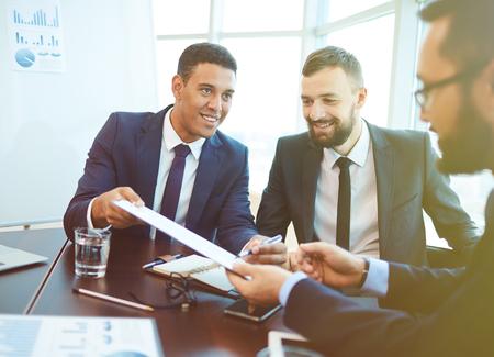 Jonge zakenman die zijn partner op contract na onderhandeling ondertekenen Stockfoto
