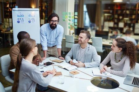 reunion de trabajo: Oficinistas modernos felices en discusiones sobre planes e ideas en la reunión