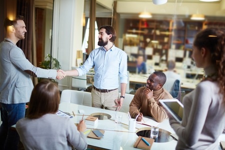 handshaking: Happy businessmen handshaking in office with colleagues near by Stock Photo