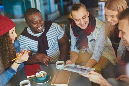 casual woman: Happy guys and girls looking at touchpad held by one of friends