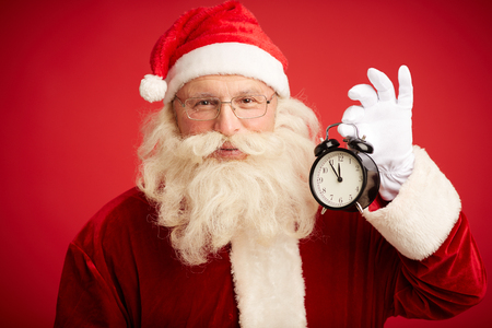 holiday tradition: Happy man in costume of Santa Claus holding alarm-clock and looking at camera Stock Photo