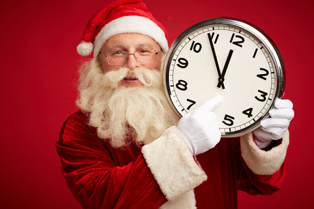 five to twelve: Happy Santa holding clock showing five minutes to twelve