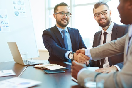 business  deal: Asian businessman handshaking with partner after negotiation Stock Photo